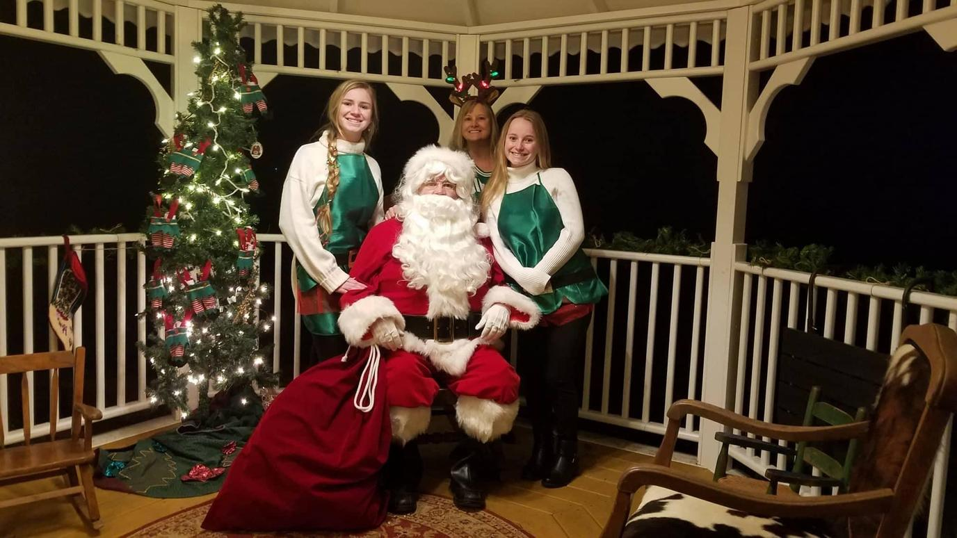 Santa Claus and elves pose for a pet photos with Santa event.
