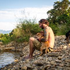Man and Dog Sit on Rocks