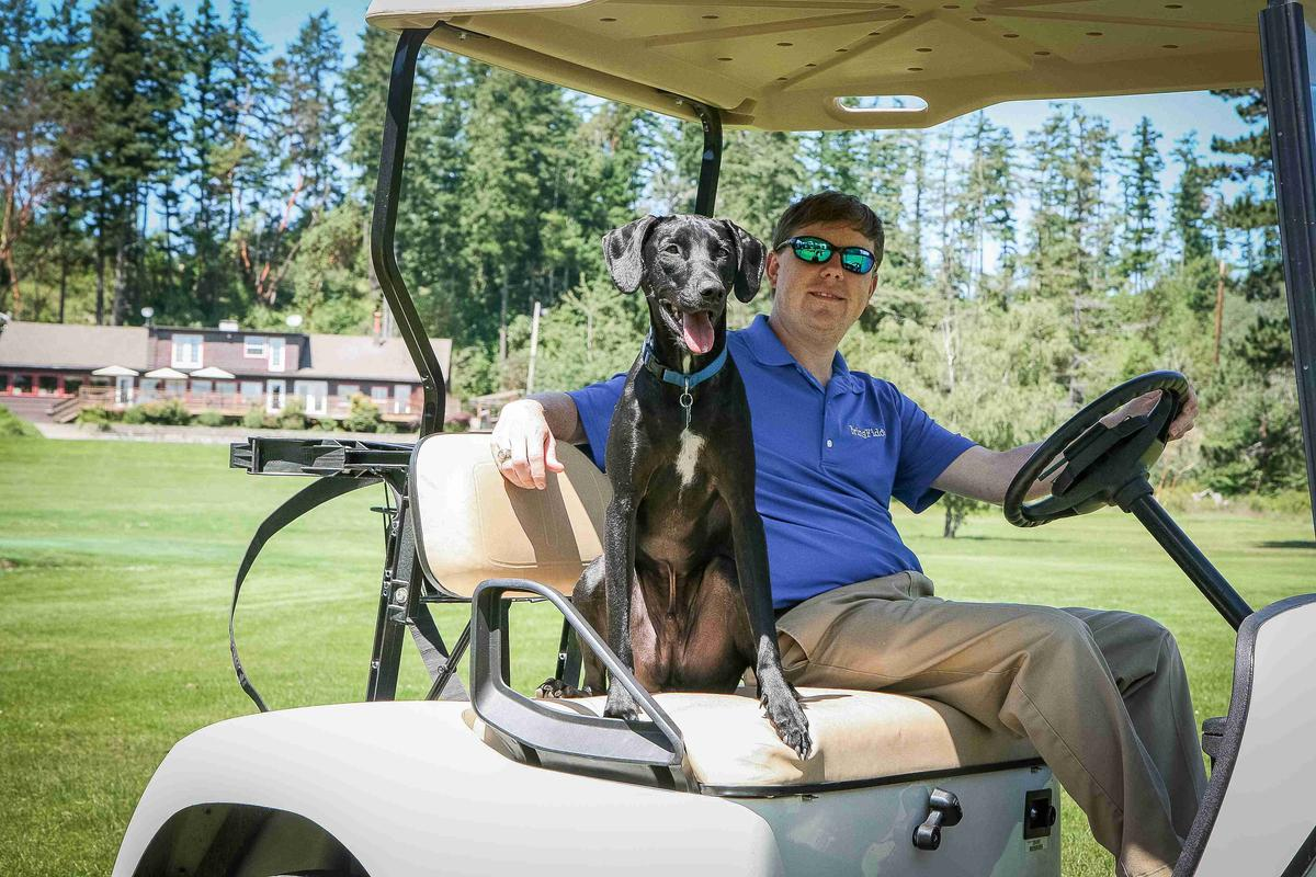 Man and His Dog Ride on a Golf Cart