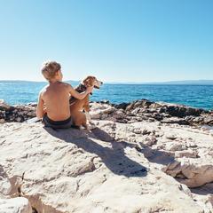 Boy with a Beagle on a Rocky Coastline