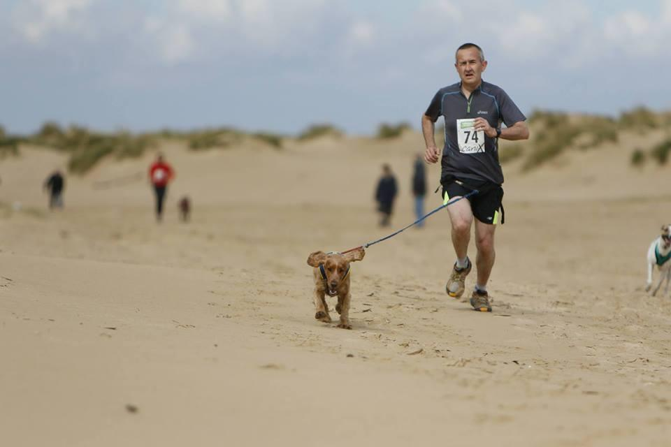 A man and his dog compete at a Canicross event.