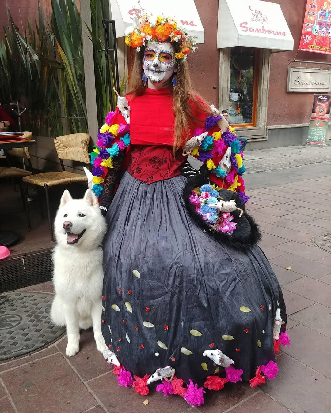 """A dog poses with """"La Catrina"""" on Day of the Dead."""