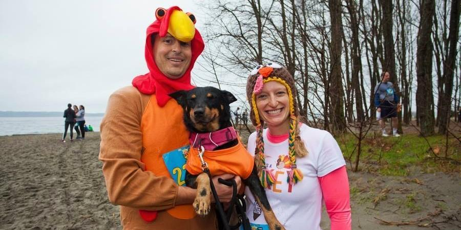A Man Dressed as a Turkey Poses With His Dog at the Seattle Turket Trot.
