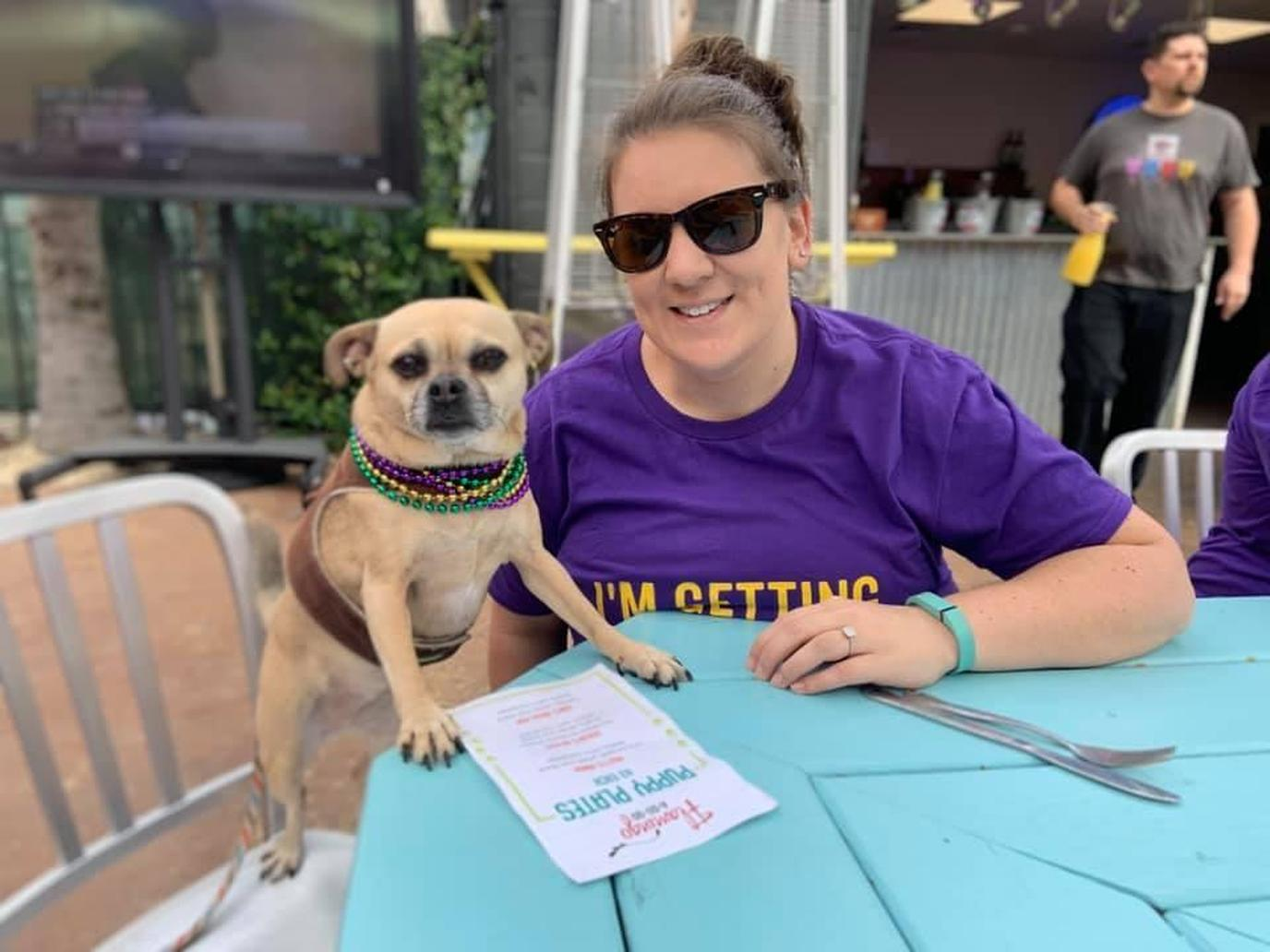 A Woman and a Dog Sit on the Dog-Friendly Patio of Flamingo A-Go-Go in Pet-Friendly New Orleans.
