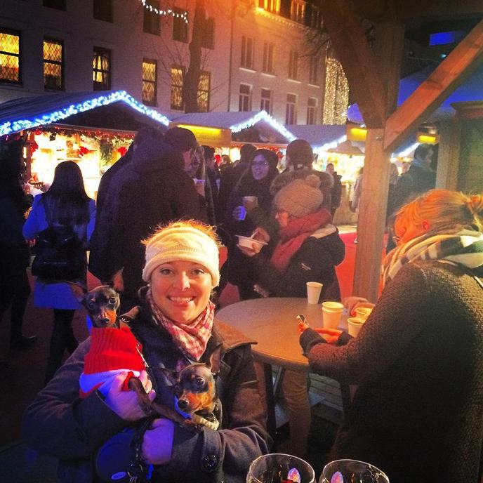 A Woman and Two Miniature Pinchers Visit a Pet-Friendly Christmas Market in Belgium.