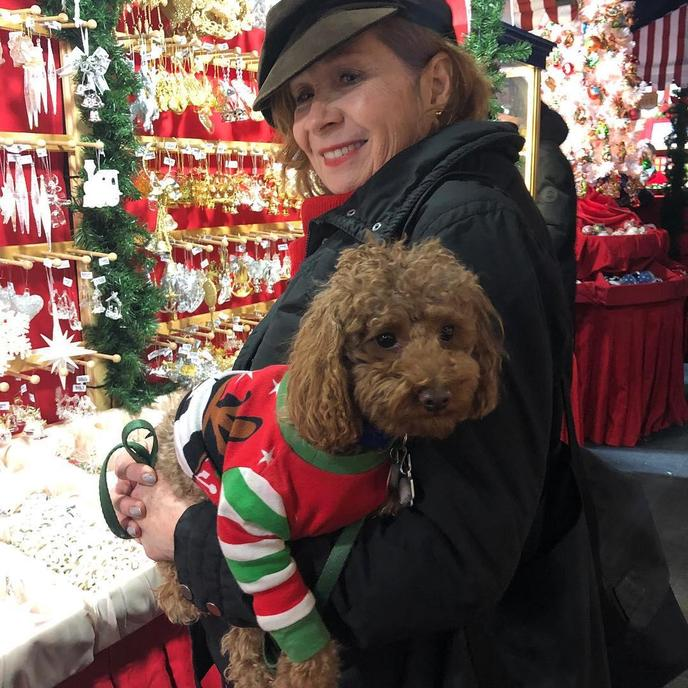 A Woman Takes a Photo WIth a Dog Wearing a Christmas Sweater at a Pet-Friendly Christmas Market.