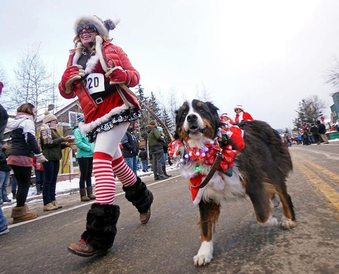 A Woman and Dog in Christmas Costumes Walk in the Breckenridge Holiday Dog Parade.