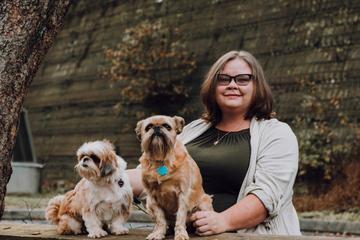 A Woman Poses With Two Dogs on Thanksgiving.