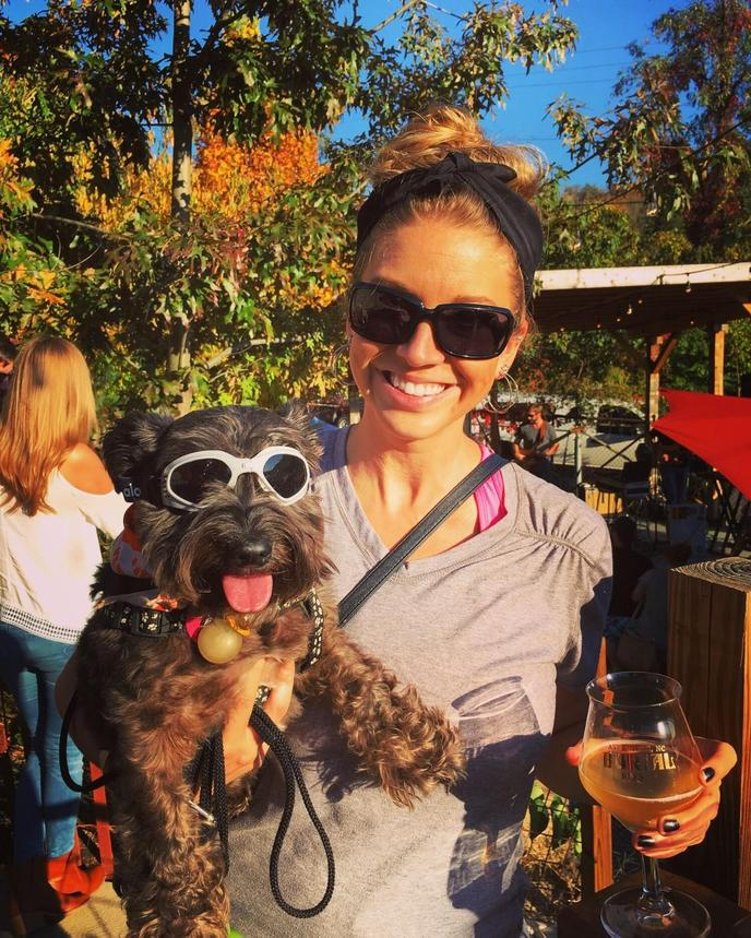 A Woman and Dog Both Wear Sunglasses.