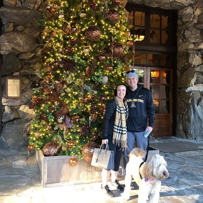A Couple and Dog Take a Photo By a Christmas Tree at a Pet-Friendly Resort Near Blue Ridge Parkway.