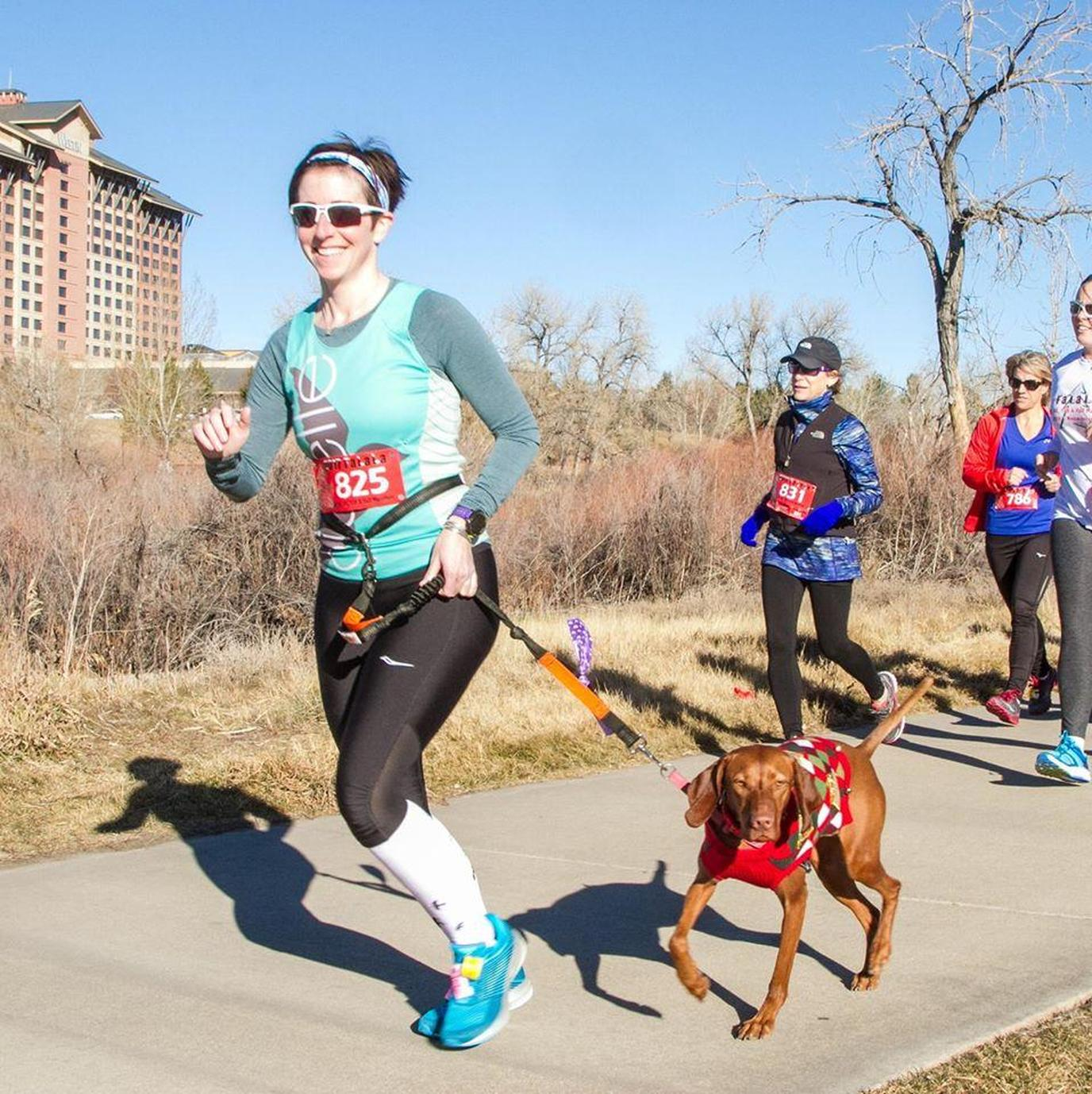 A Woman Runs With Her Dog in a Pet-Friendly Christmas Race in Colorado.