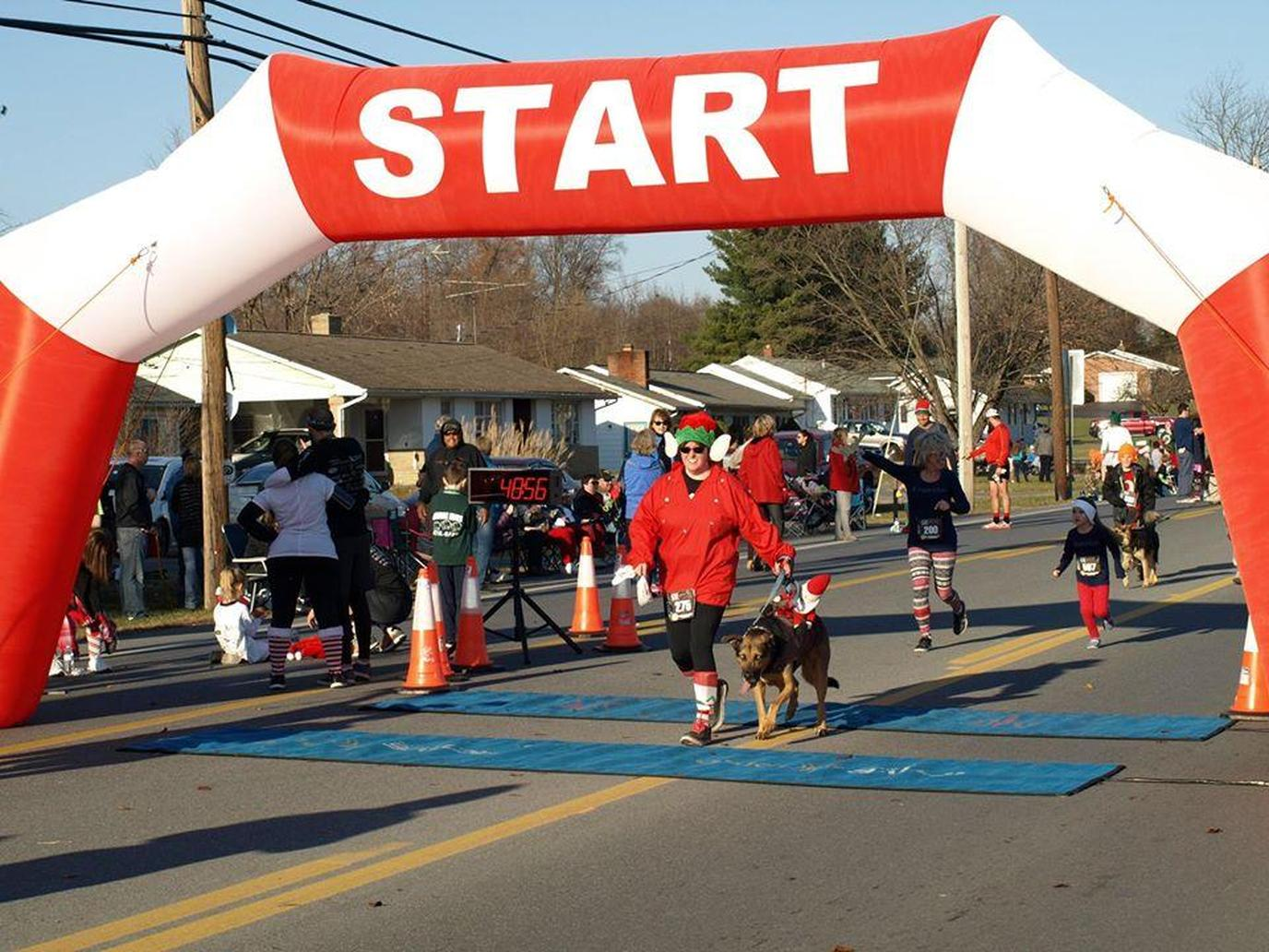 A Woman and Dog Cross the Finish Line at a Pet-Friendly Christmas Race in Inwood, West Virginia.
