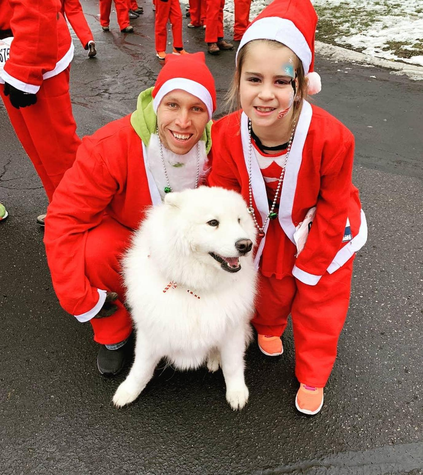 A Man and Girl Dressed as Santas Pose With a Dog at a Pet-Friendly Christmas Race in Michigan.