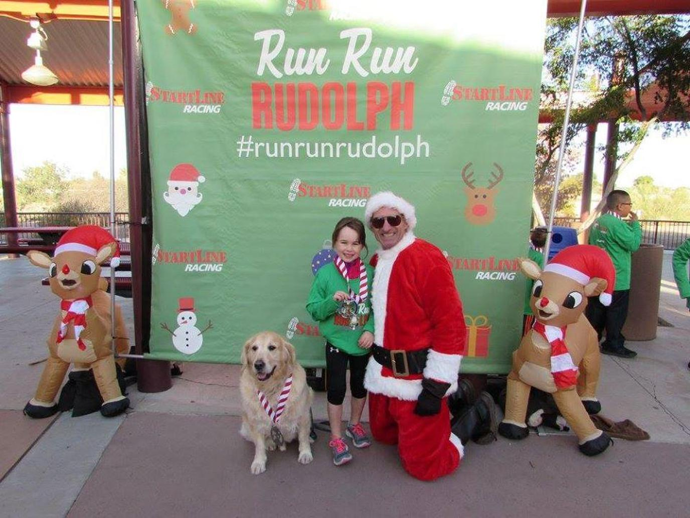 A Man Dressed as Santa Poses With a Girl and a Dog at a Pet-Friendly Christmas Race in Arizona.