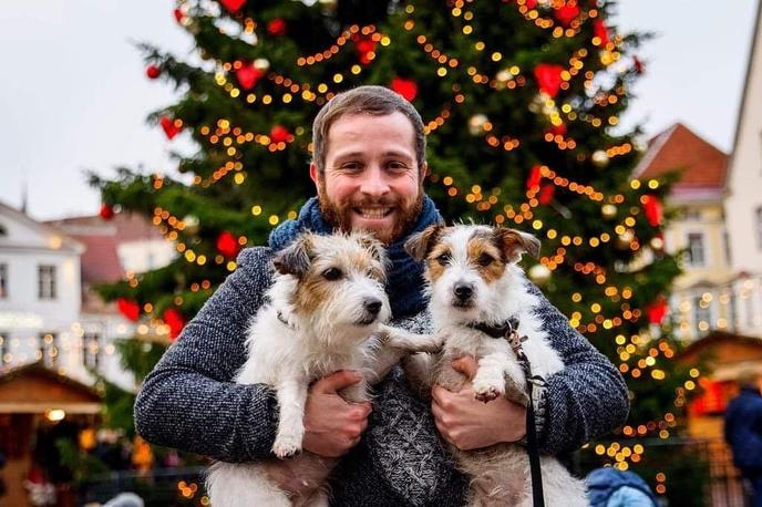 A Man and Two Jack Russel Terriers Pose at a Pet-Friendly Christmas Market.