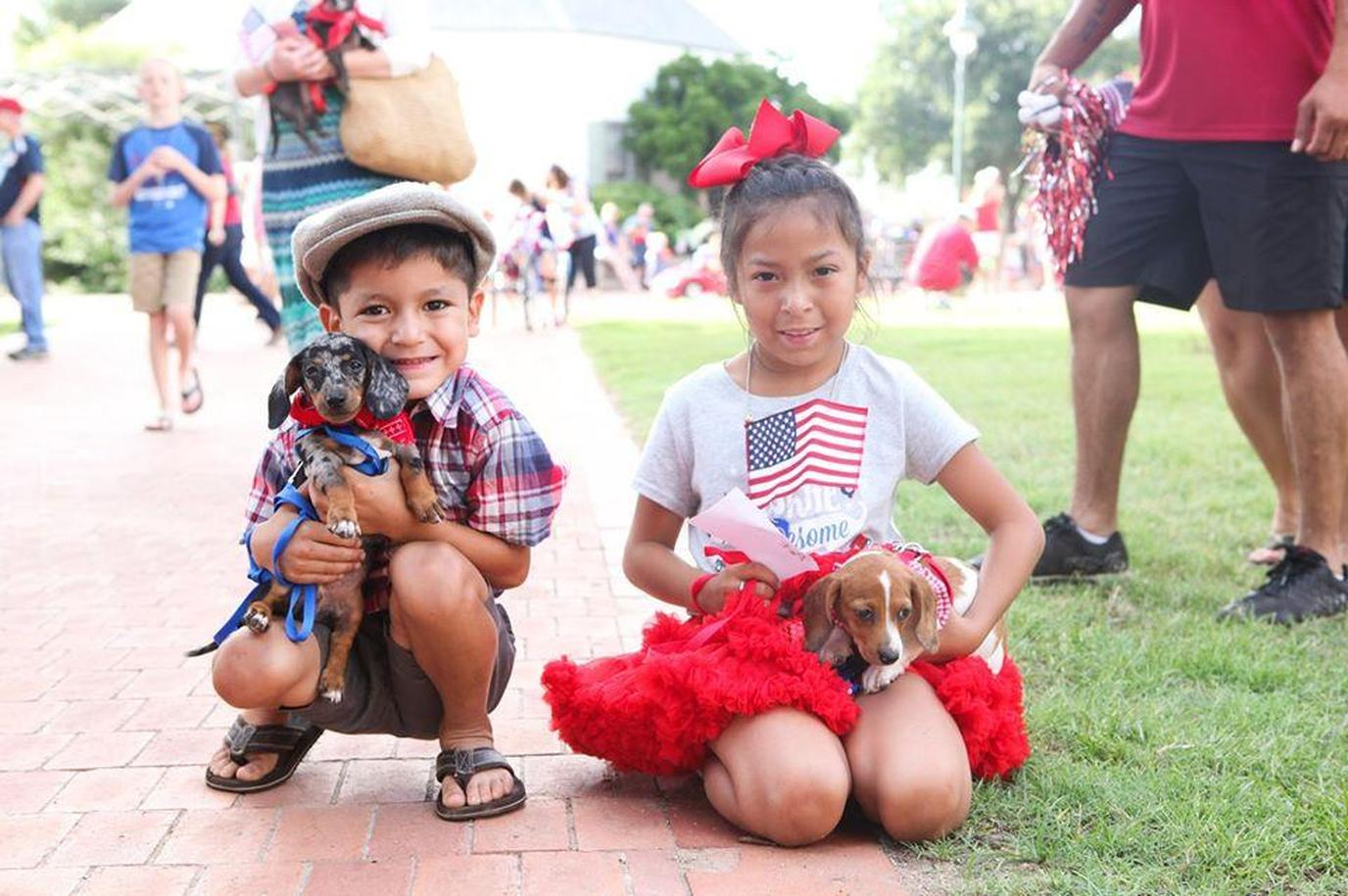 A Girl and Boy Each Hold a Dachshund Puppy in Dog-Friendly Fredericksburg.