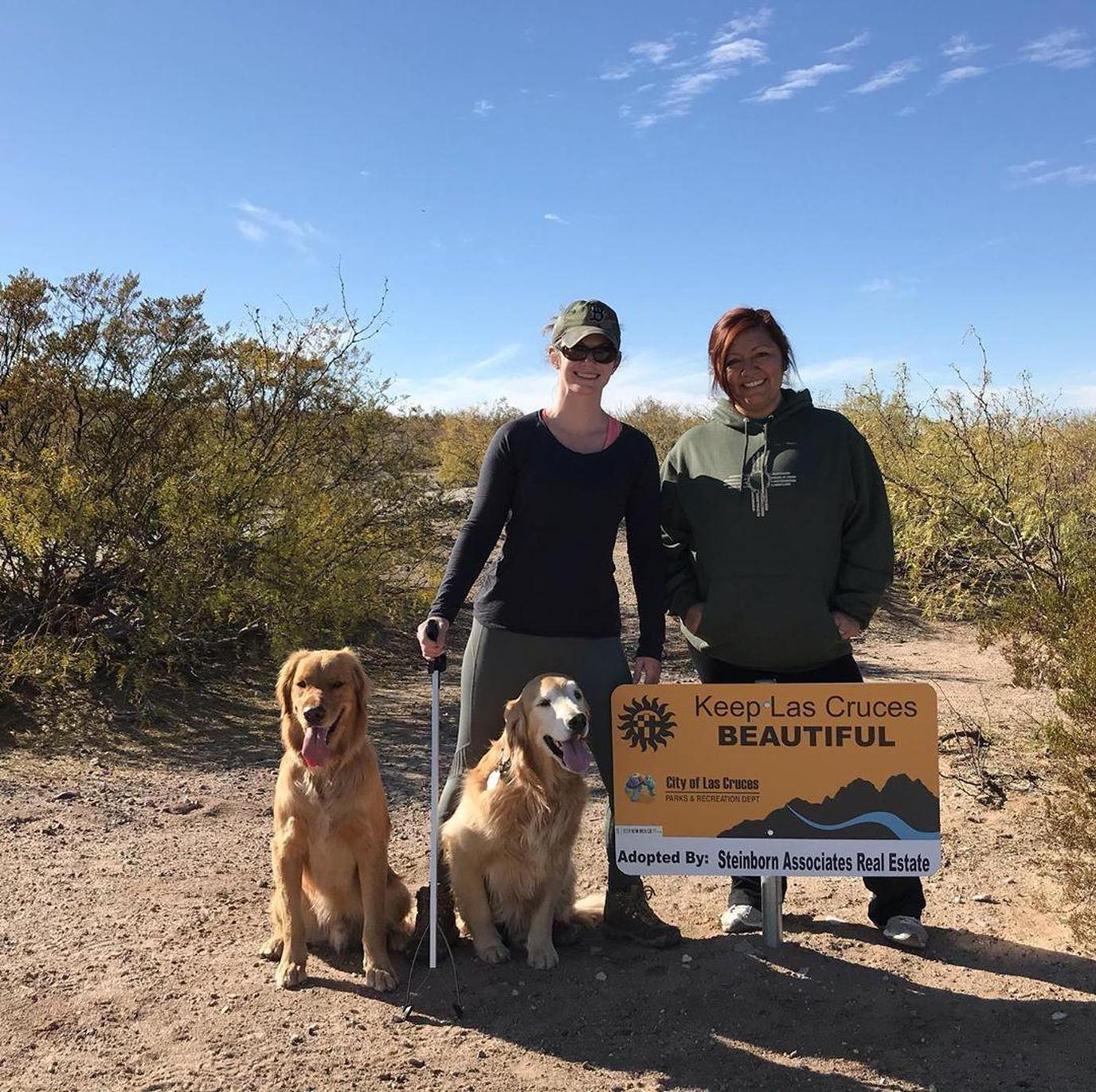 Two Woman and Two Golden Retreivers Stand By a Sign That Says Keep Las Cruces Beautiful.