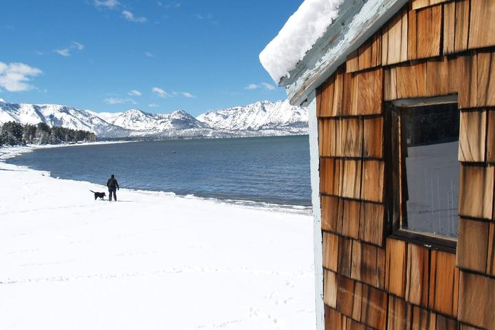 A man and a dog stand beyond a cabin on the snow-covered shores of Lake Tahoe.