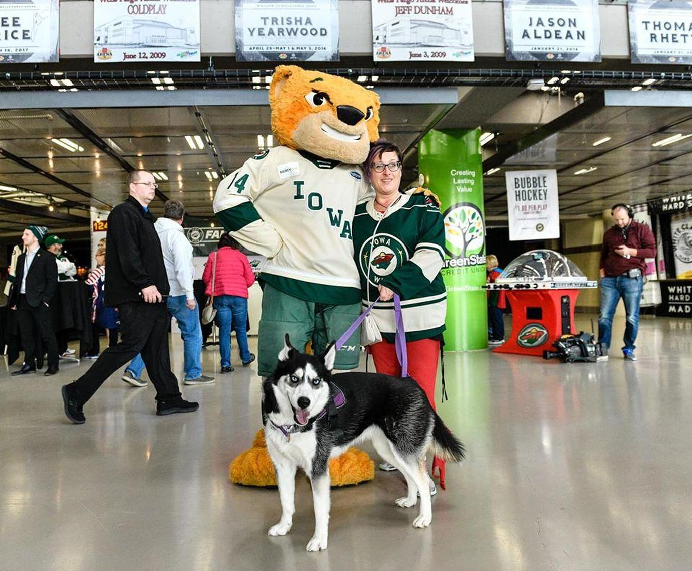 A Woman and Her Dog Poses With a Mascot at a Dog-Friendly Hockey Game in Iowa.