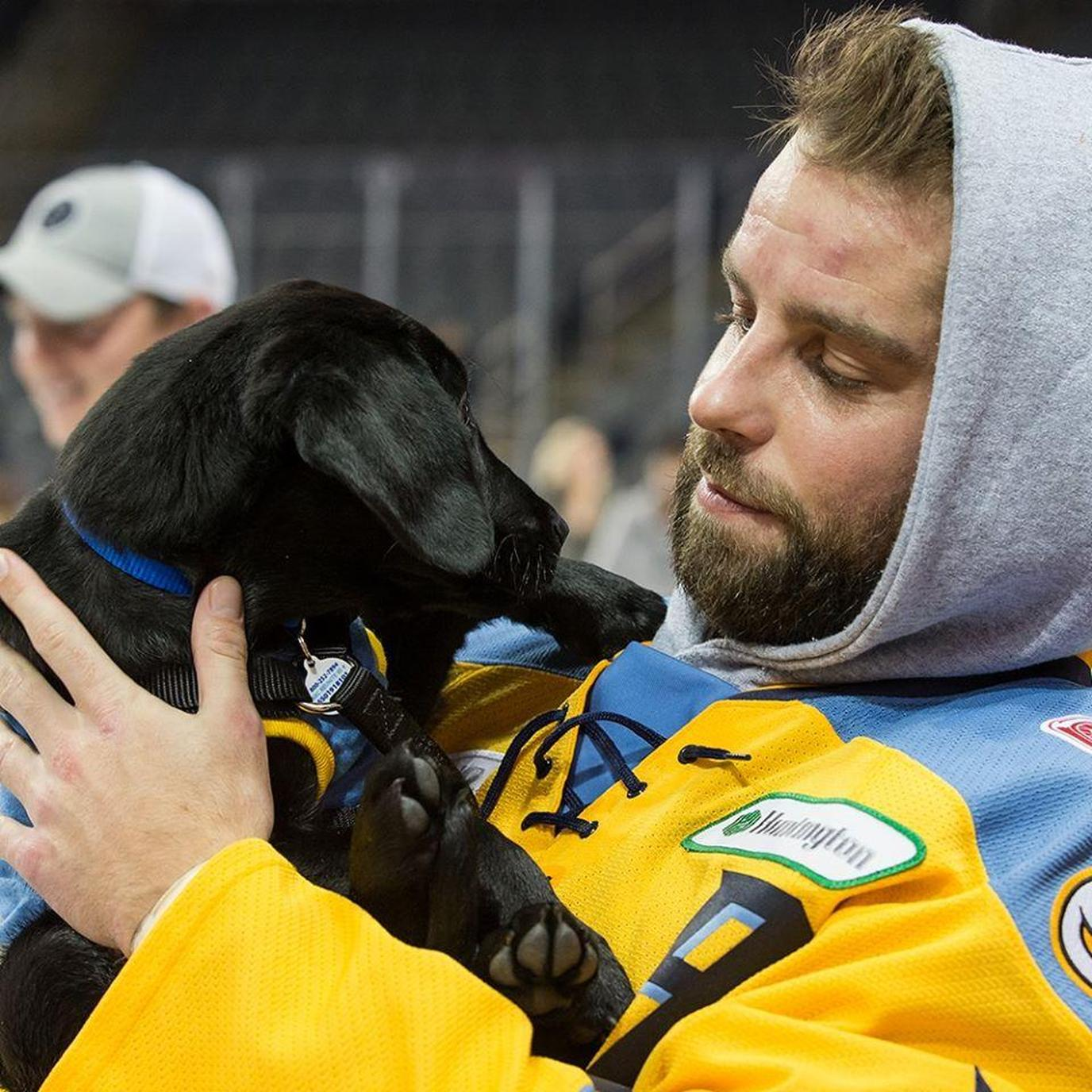 A Man Hugs a Dog From His Seat at a Dog-Friendly Hockey Game in Ohio.