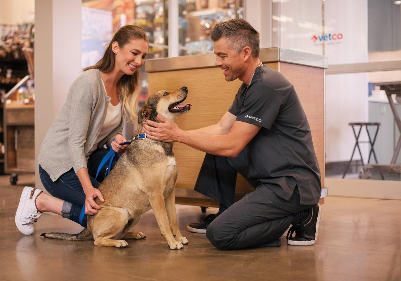 A Petco Associate Greets a Leashed Dog and His Mom Outside of a Vetco Office.
