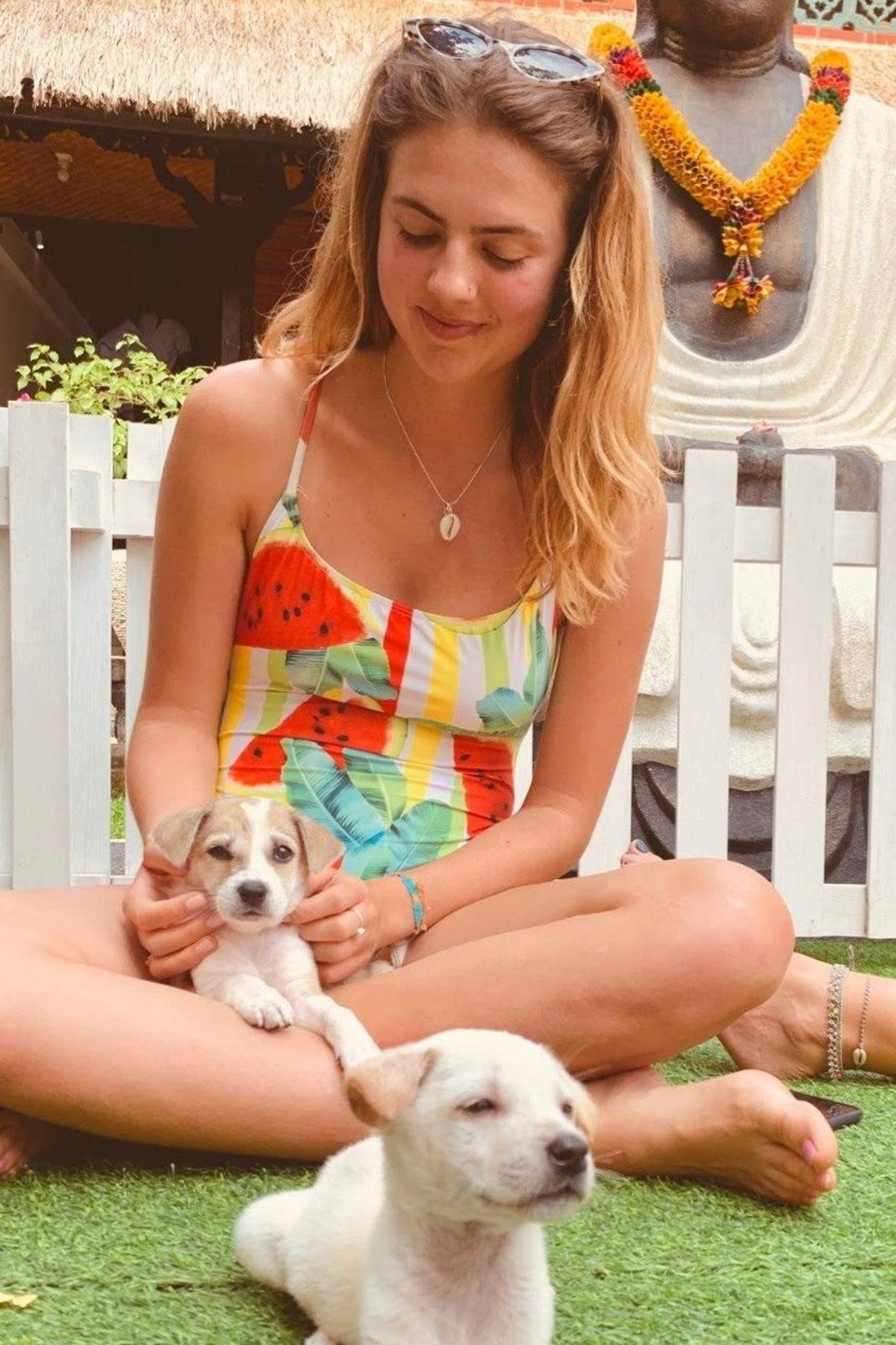 A Woman Cuddles a Labrador Puppy During a Pet-Friendly Airbnb Experience in Bali.