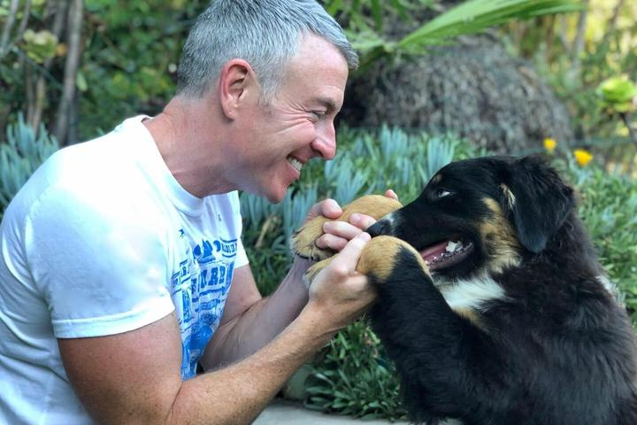 Pet Psychic Michael Burke Holds the Paws of a Fuzzy Black Dog.