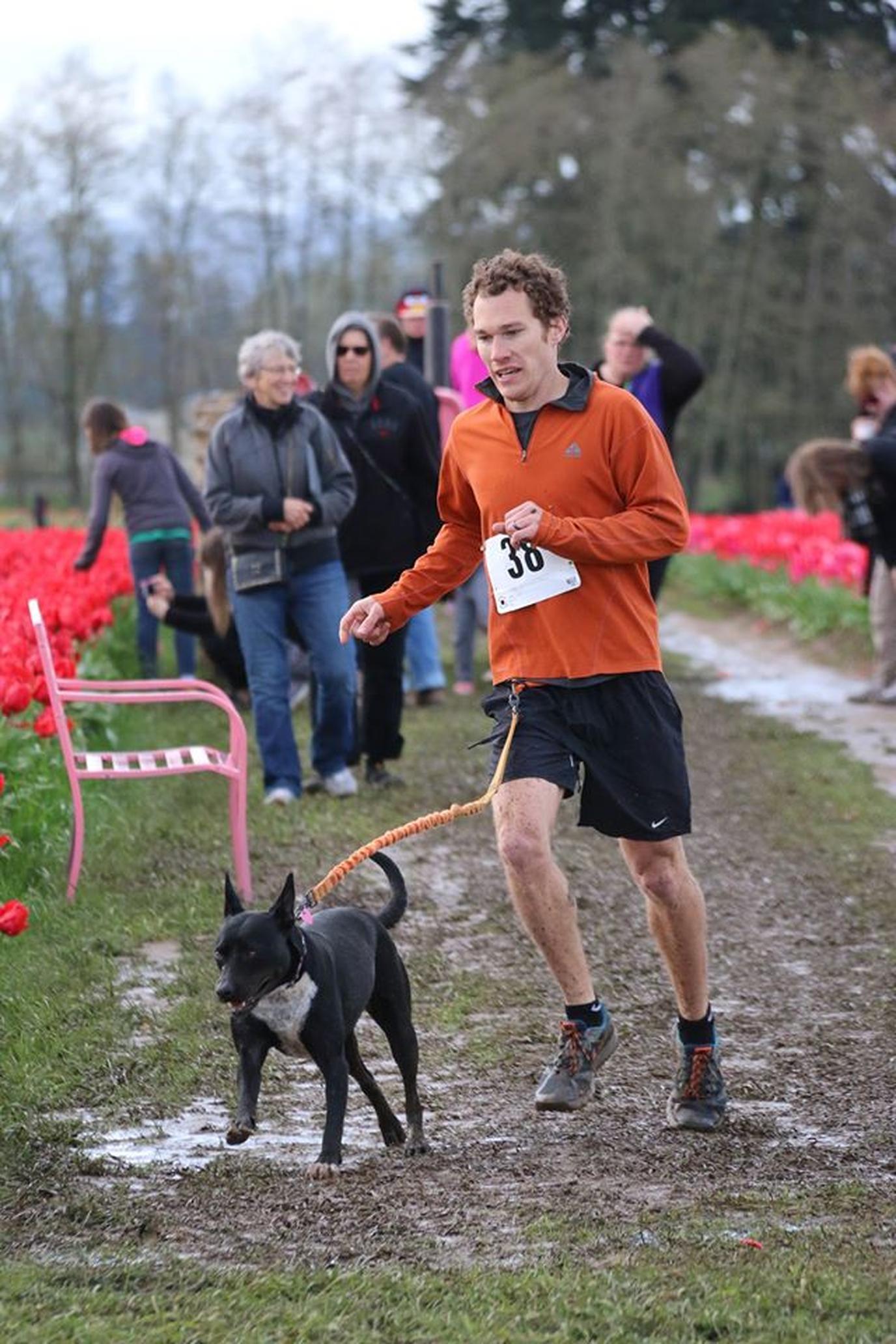 A Man Runs Through the Mud With His Dog at a Pet-Friendly Spring Run in Woodburn.