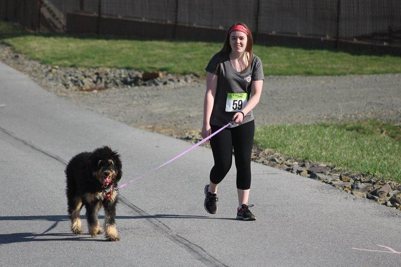 A Woman and a Fuzzy Dog Participate In a Dog-Friendly Spring Run.