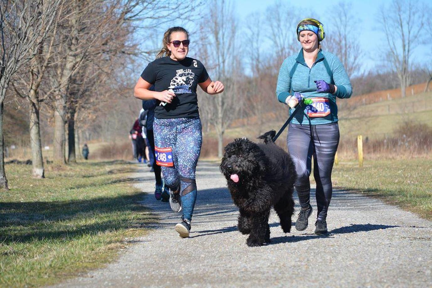 Two Women Run Down a Paved Trail With a Dog During a Pet-Friendly Spring Run in Zanesville.
