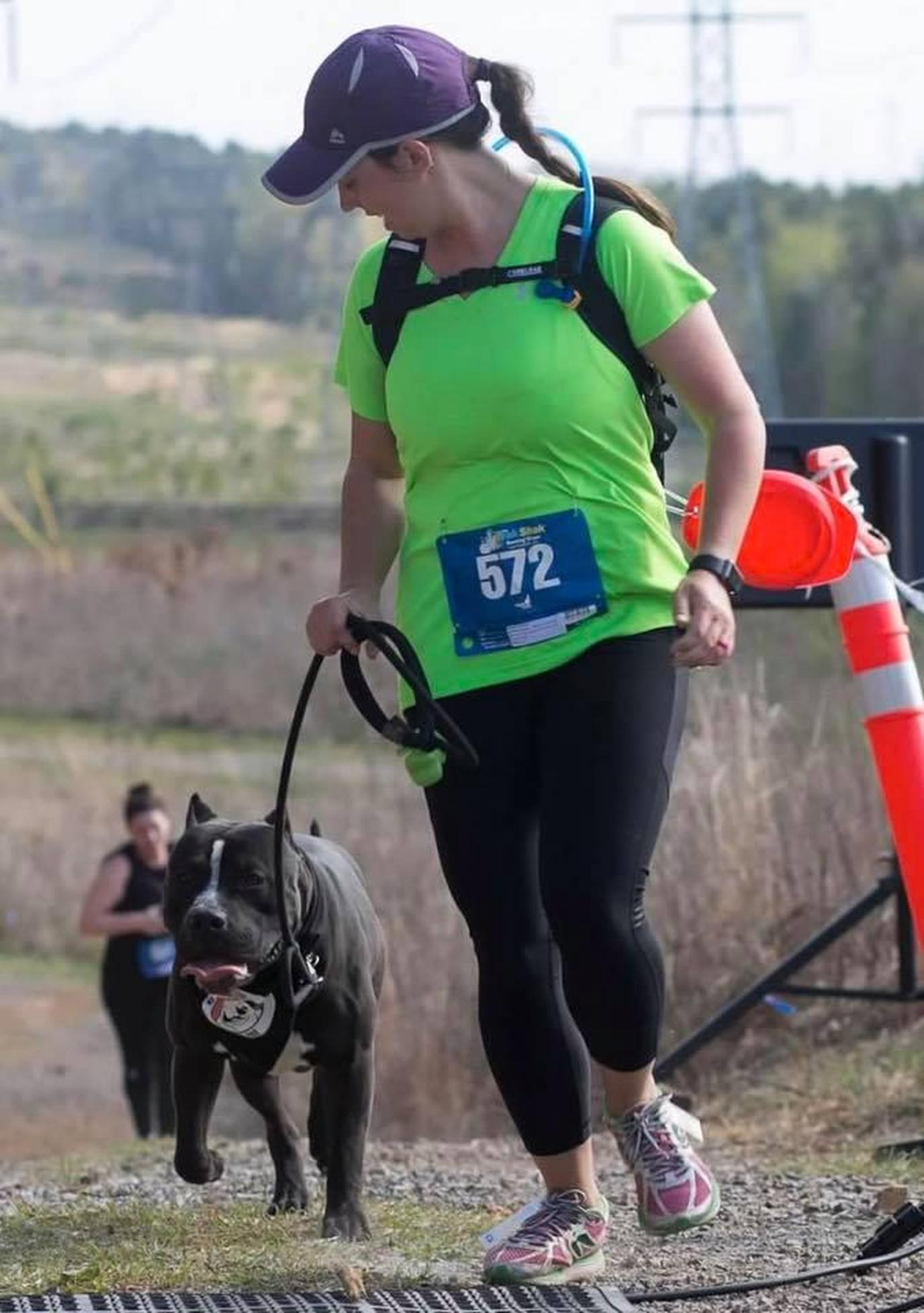 A Woman and Pit Bull Run For the Dog-Friendly Running of the Bulls in Birmingham.