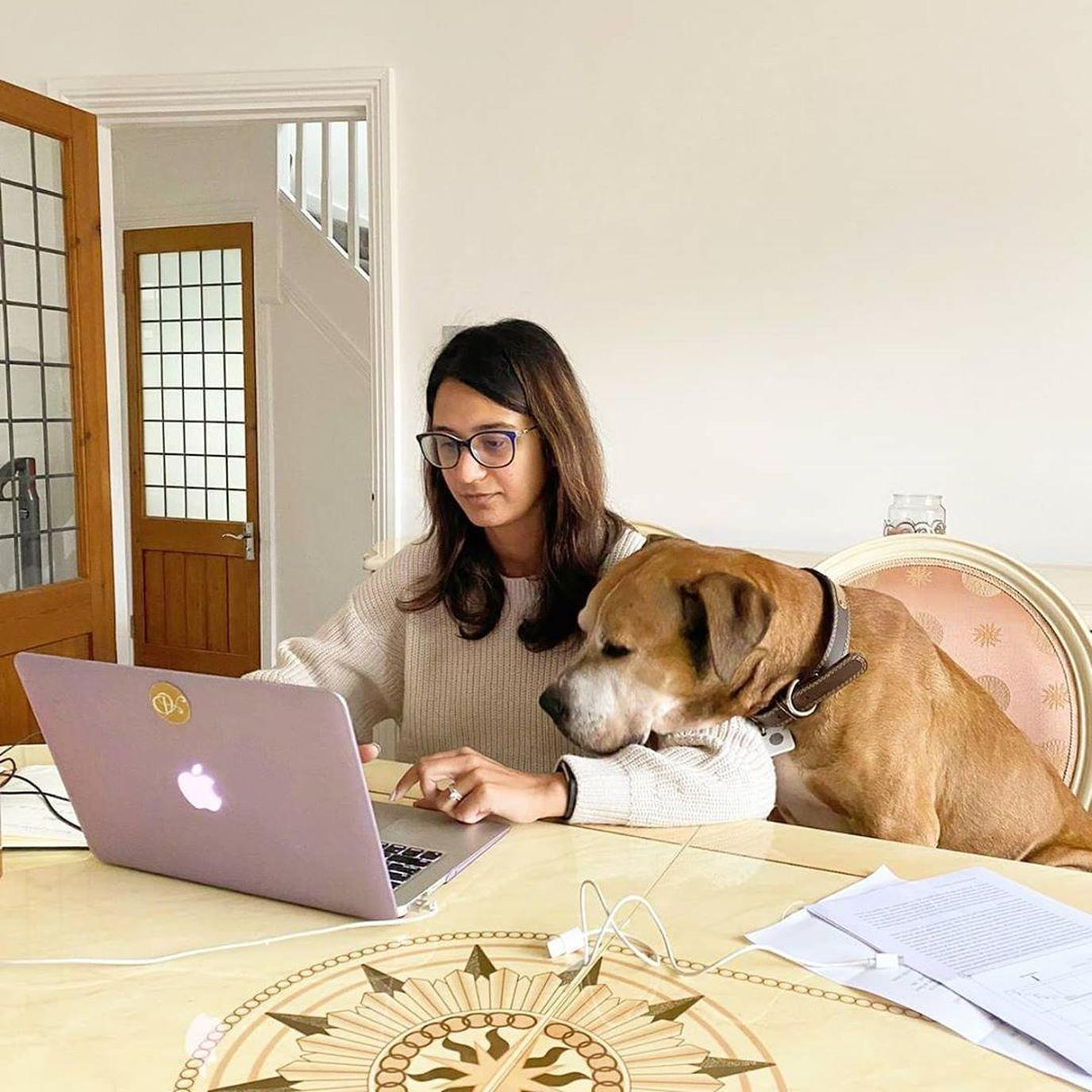 A Dog Looks Over a Woman's Shoulder as She Works From Home.