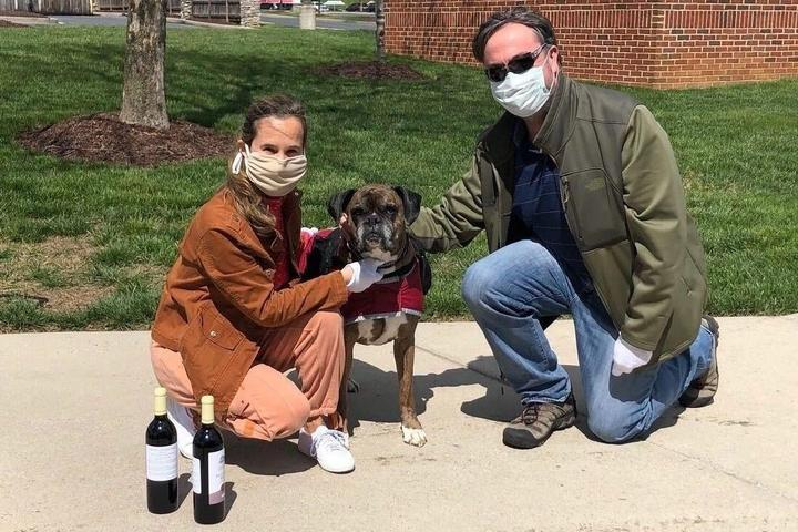 Two Masked Humans Pose With a Dog.