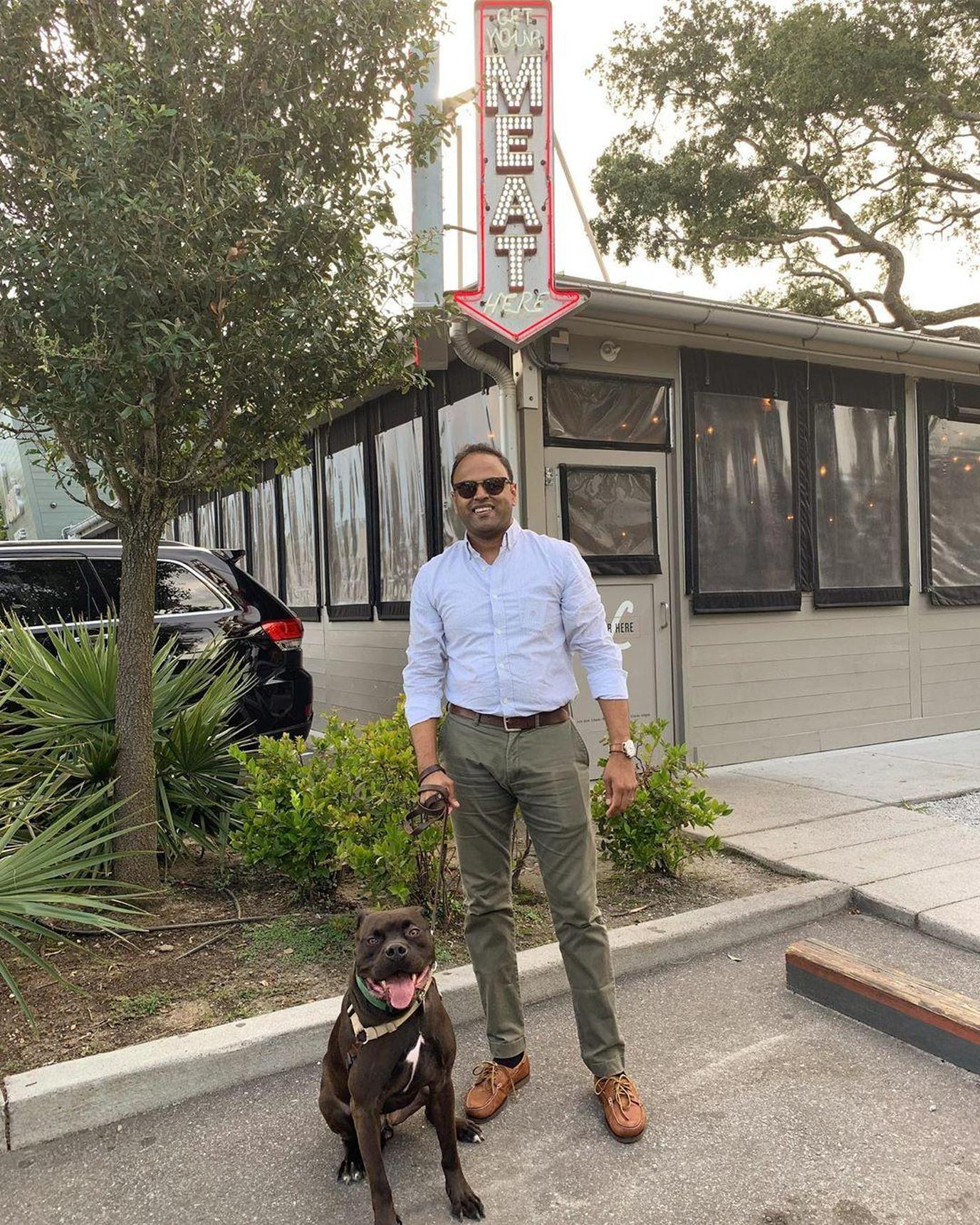 A Man and Dog Stand in Front of Lewis Barbecue, a Pet-Friendly BBQ Restaurant in Charleston.