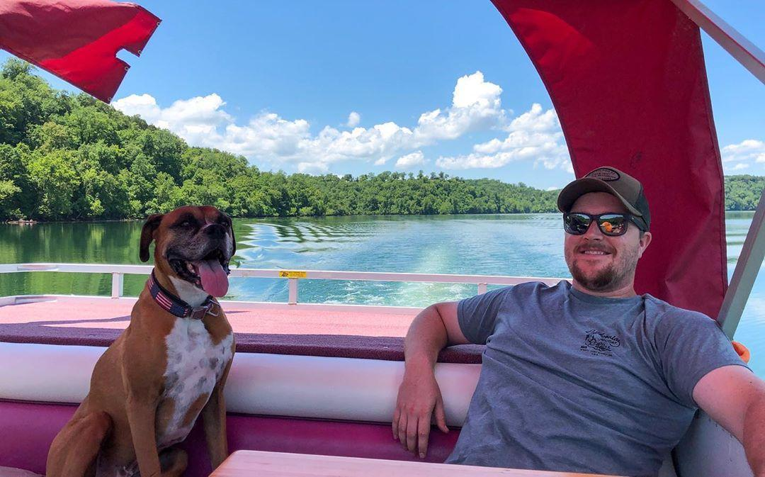 A dog relaxes on a pontoon with his dad on a sunny day.