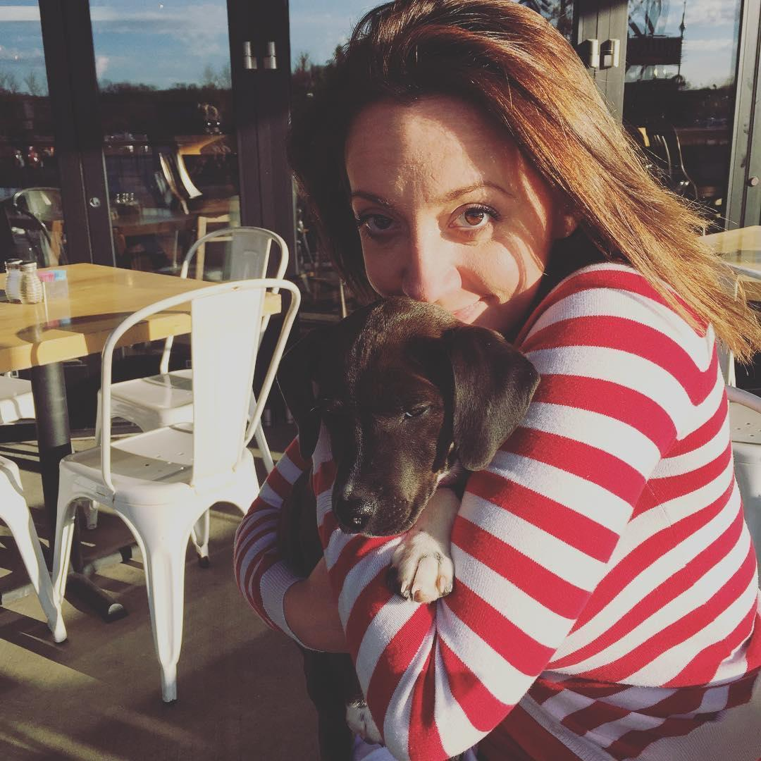 A woman in a striped shirt snuggles a puppy on the patio of the dog-friendly Black Oak Grill.