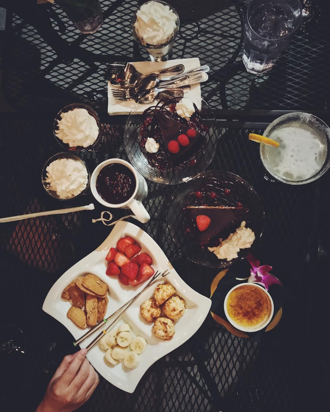 A patio table laden with drinks and desserts.