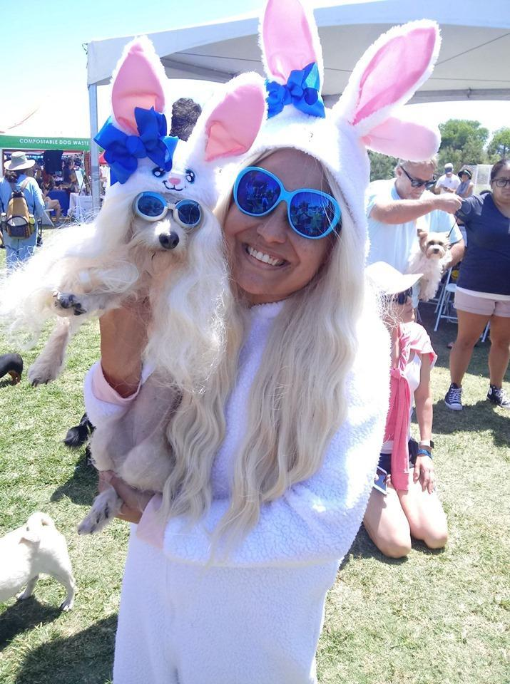 A Woman and Her Dog Dress in Matching Halloween Costumes as Bunnies.